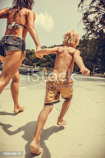 Woman and son running along the tropical beach
