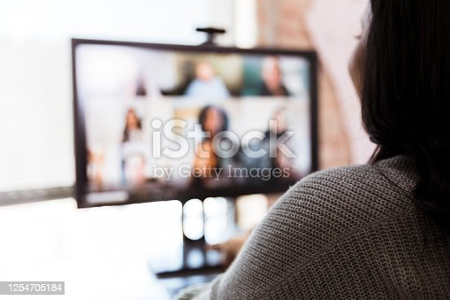 In this defocused photo, an unrecognizable woman and her team meet via video conferencing.