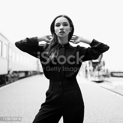 Black and white head and shoulders art portrait on the platform against trains background. Sexual young girl in vintage high waist pants and fashion shirt straightens her hair