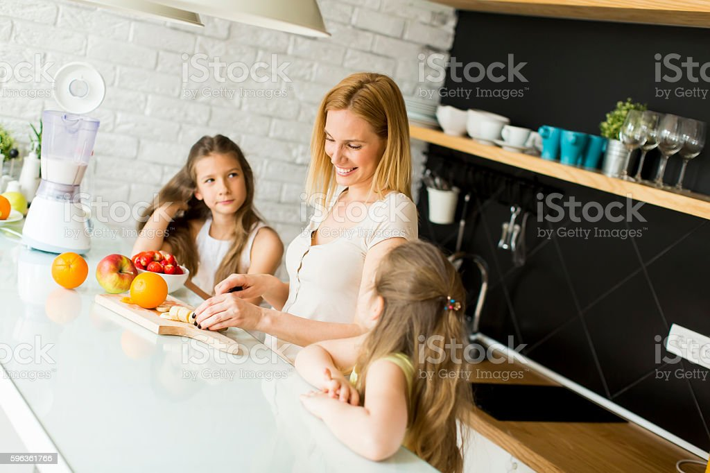 Woman and two girls in the kitchen royalty-free stock photo