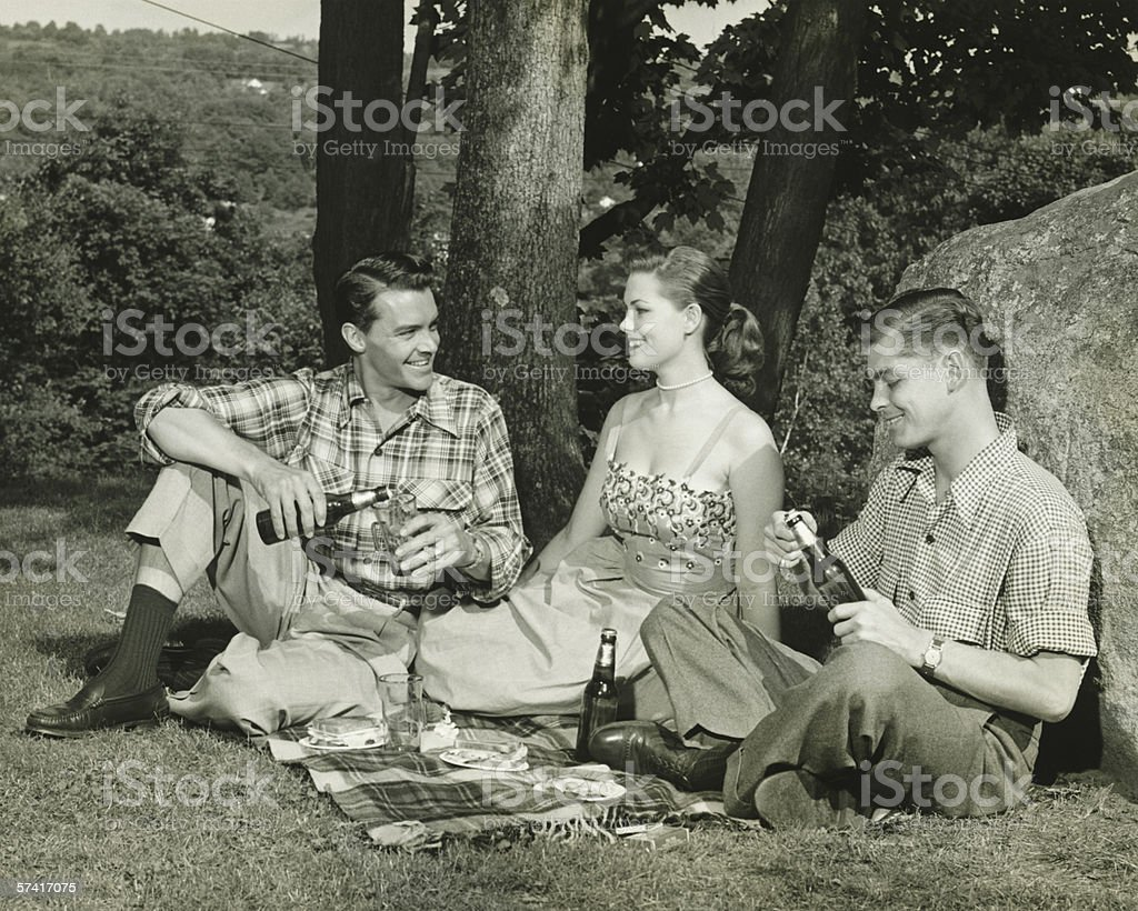 Woman and two men picnicking, (B&W) royalty-free stock photo