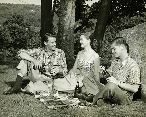 Woman and two men picnicking, (B&W) stock photo