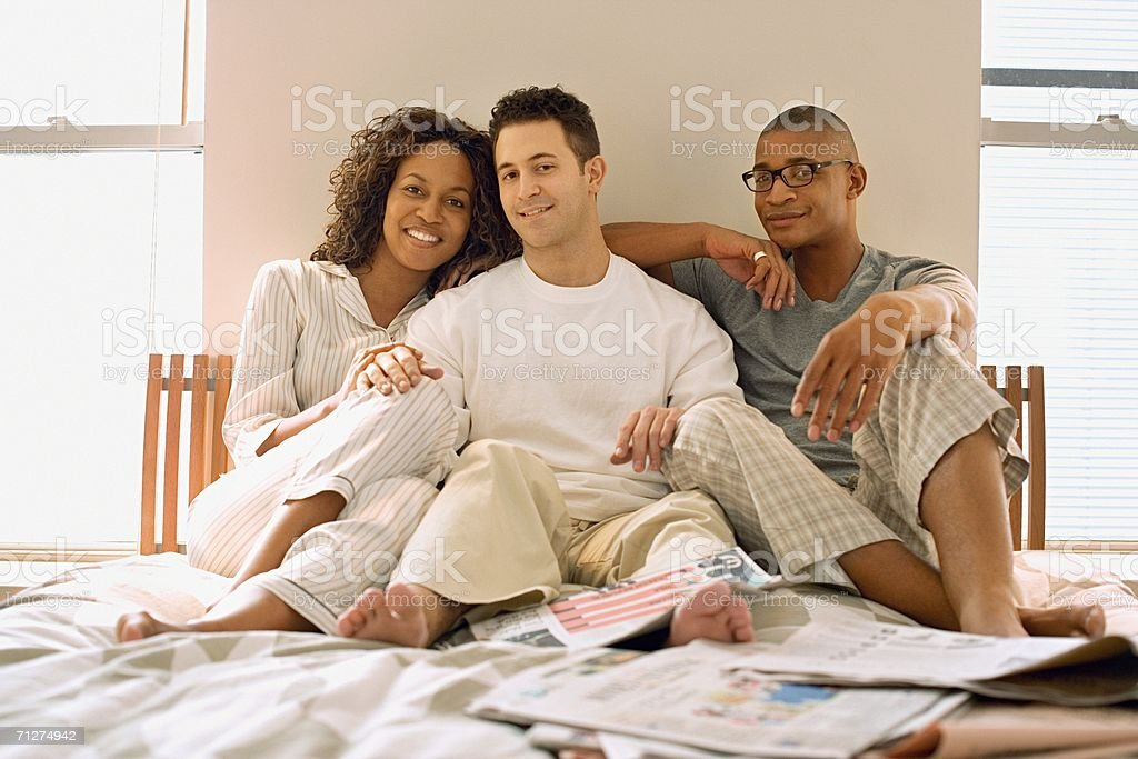 Woman and two men sitting on bed stock photo