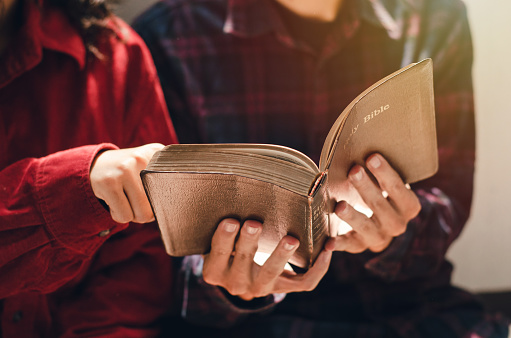 A woman and two men were studying and reading the Bible. That is Christian love