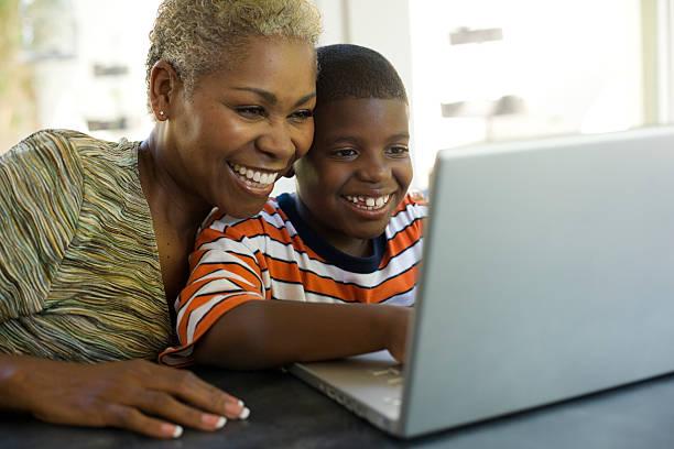Frau und junge junge sitzt auf laptop-computer – Foto