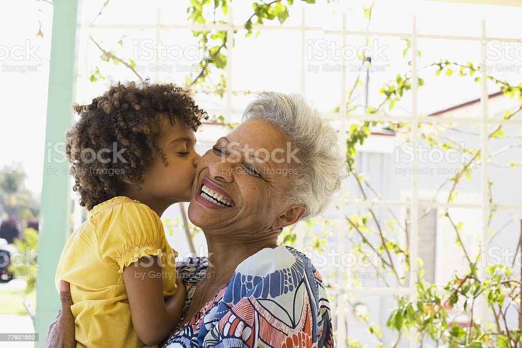 Woman and young girl embracing outdoors