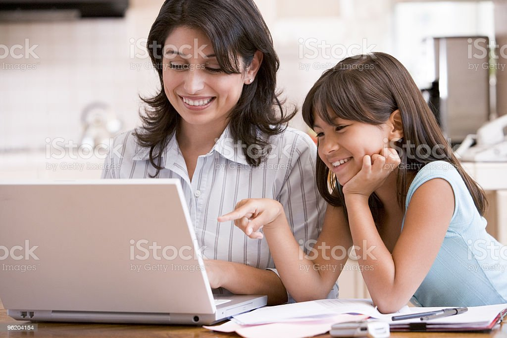 Woman and young girl in kitchen with laptop stock photo