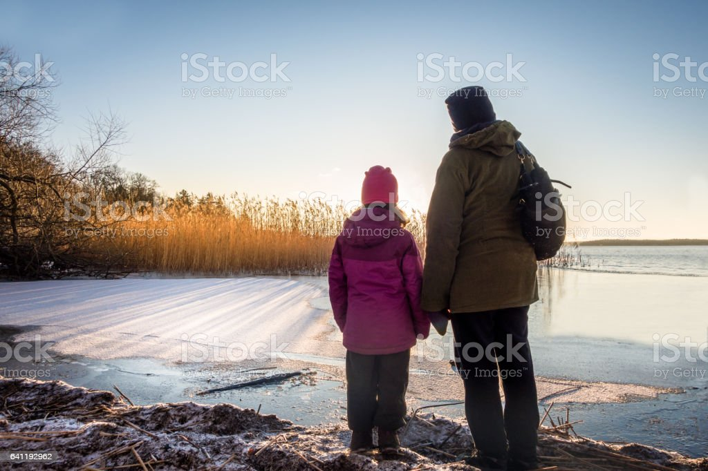 Woman and young girl looking at beautiful winter sunset against icy water and blue sky, late afternoon. royalty-free stock photo