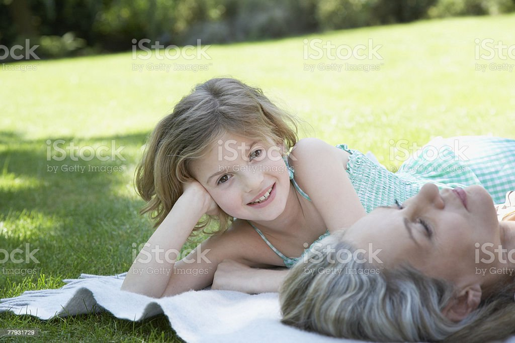 Woman and young girl lying outdoors on a blanket royalty-free stock photo