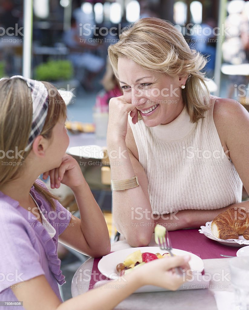 Woman and young girl on outdoor patio eating meal royalty-free stock photo