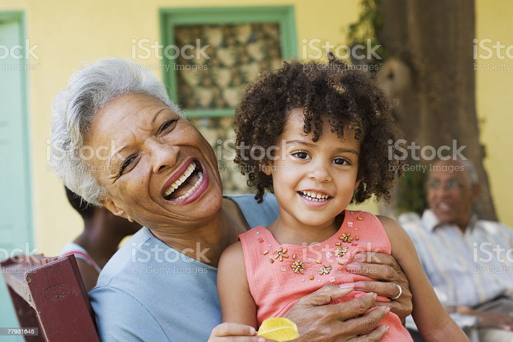 Woman and young girl outdoors with people in background stock photo
