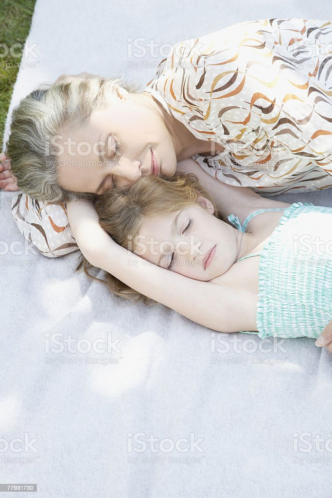 Woman and young girl sleeping outdoors on blanket royalty-free stock photo
