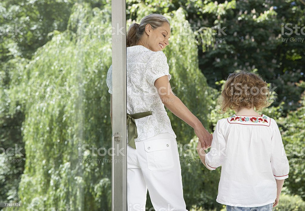 Woman and young girl standing outside a large glass door royalty-free stock photo