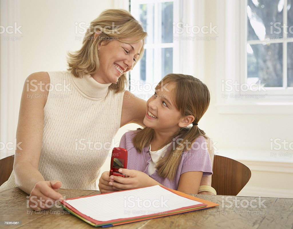 Woman and young girl with mobile phone and homework at kitchen table royalty-free stock photo
