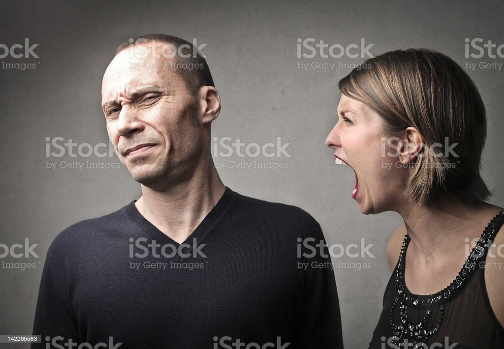 Woman angrily shouting at a man while he is disgusted stock photo