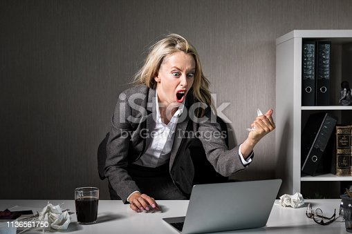 692461598 istock photo Woman angry at her laptop computer at work 1136561750