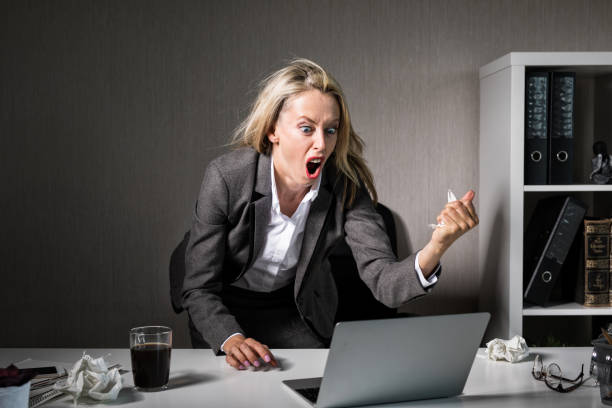 frau wütend auf ihrem laptop bei der arbeit - frustration stock-fotos und bilder