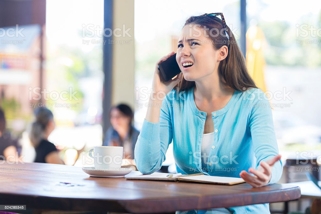 Woman annoyed by phone call in local coffee shop stock photo