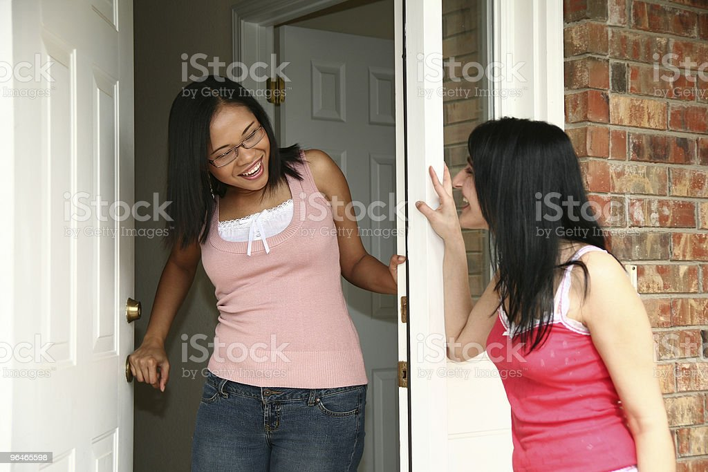 A woman answers the door to her friend royalty-free stock photo