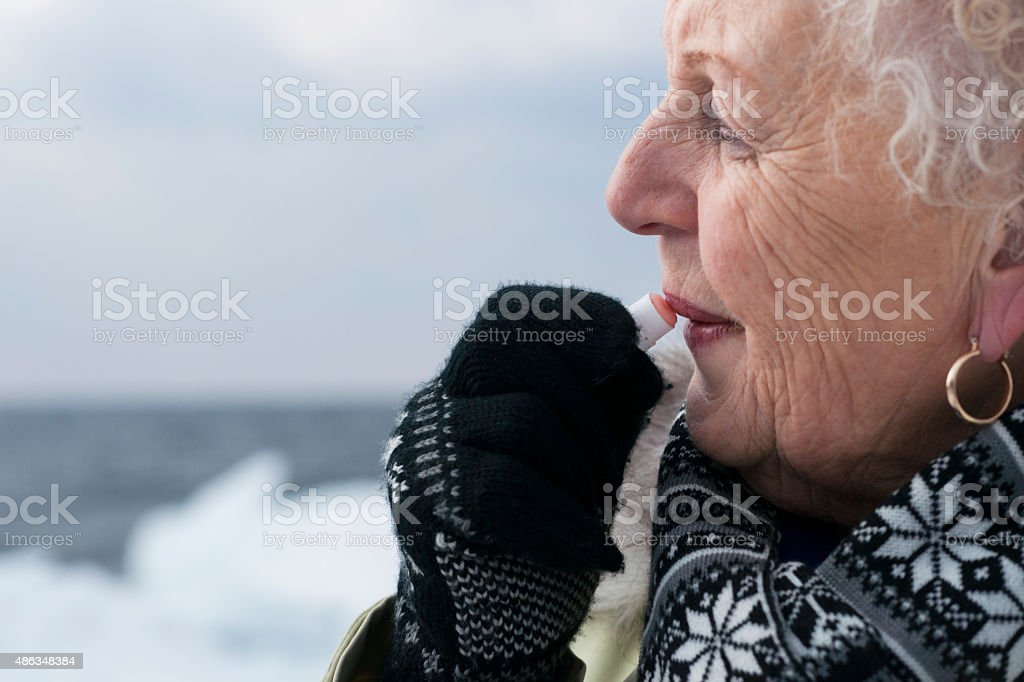Woman applies lip balm during winter stock photo