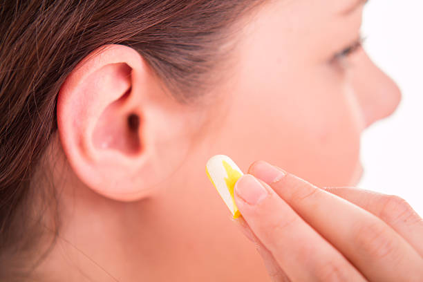 Woman apply earplugs into ea
