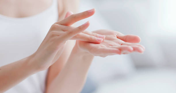 woman apply moisturizer in hand beautiful woman apply moisturizer into her hand at home beauty treatment stock pictures, royalty-free photos & images