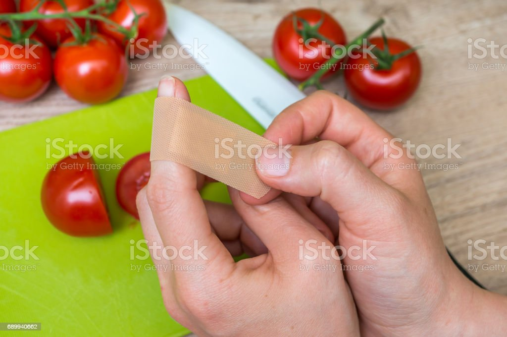 Woman apply plaster on her finger - injury in kitchen stock photo