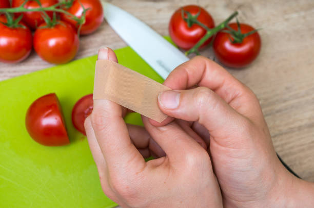 woman apply plaster on her finger - injury in kitchen - knife wound stock photos and pictures