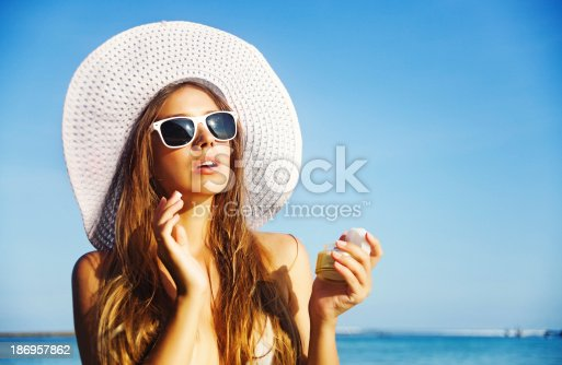 istock Woman apply sunscreen 186957862