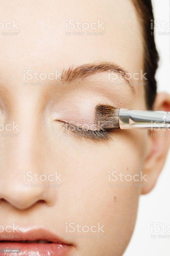 Woman applying a pale pink eyeshadow stock photo