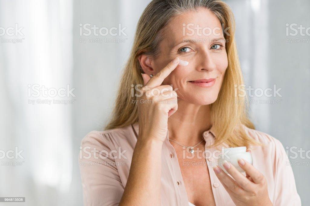 Application anti vieillissement de lotion sur le visage de femme - Photo