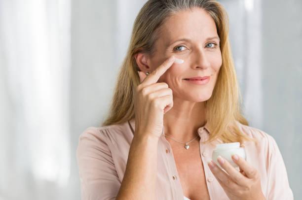Frau anti-aging-Lotion auf Gesicht auftragen – Foto