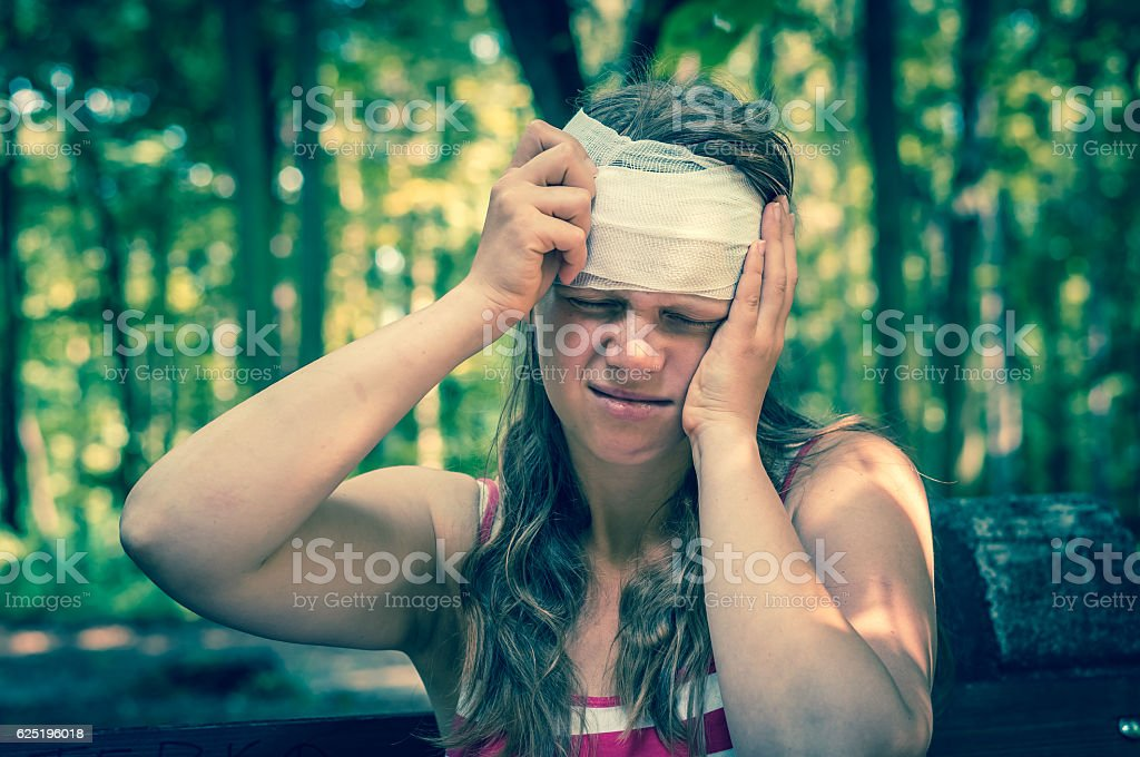 Woman applying bandage on her head after injury in nature stock photo