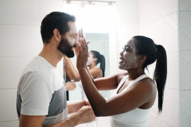 Woman Applying Beauty Mask And Skin Cleanser To Man stock photo