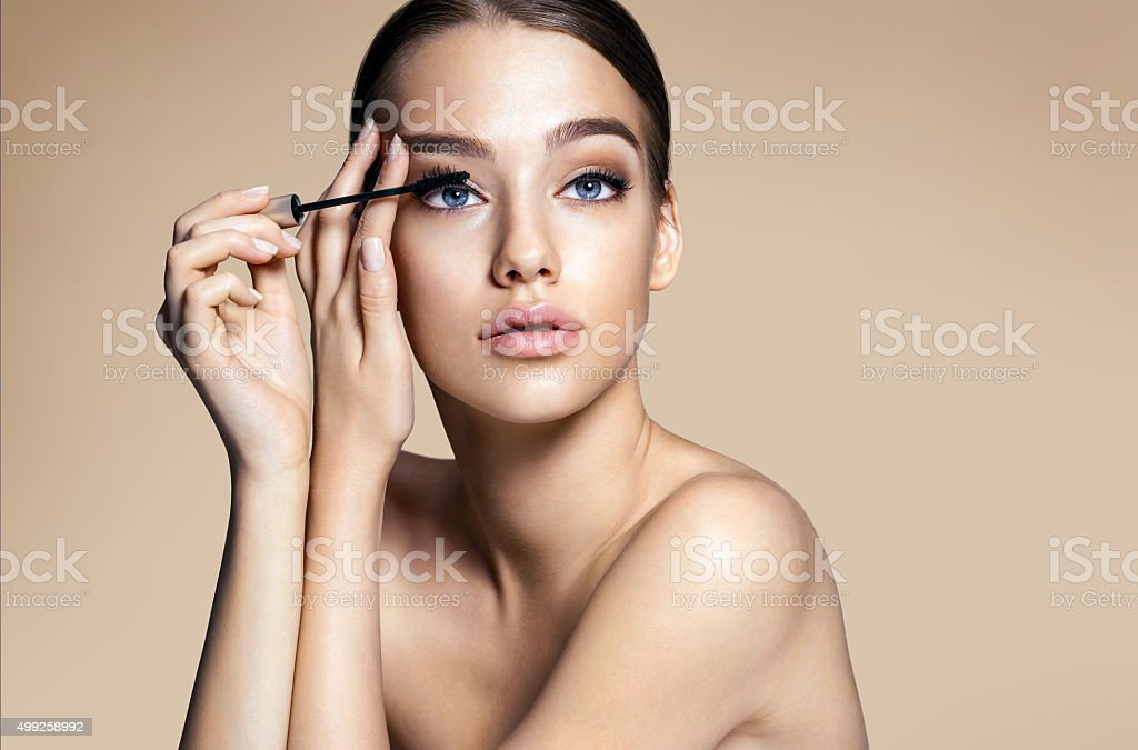 Woman applying black mascara on eyelashes with makeup brush