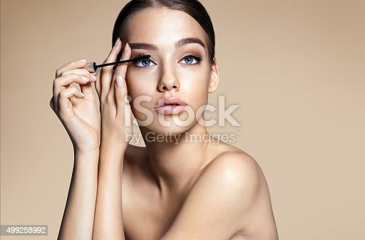 istock Woman applying black mascara on eyelashes with makeup brush 499258992