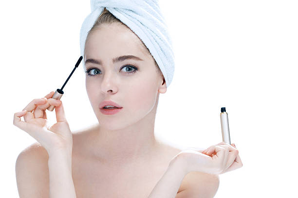 Woman applying black mascara stock photo