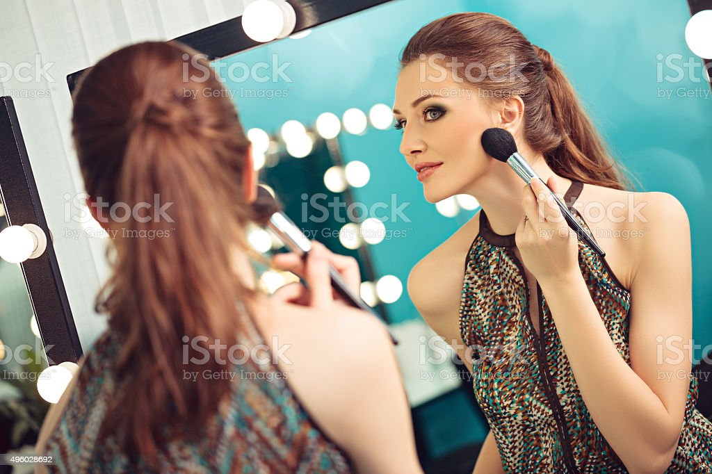 Woman applying blush or powder stock photo