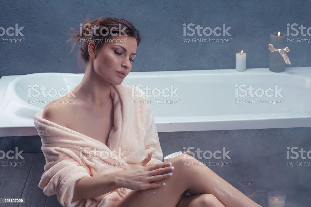 Woman applying body lotion on her legs in bathrobe stock photo
