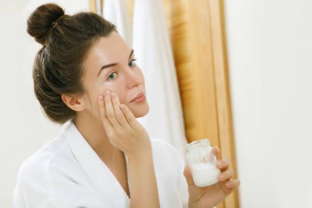 vrouw die kokosolie op haar gezicht aanbrengt - creme huid stockfoto's en -beelden