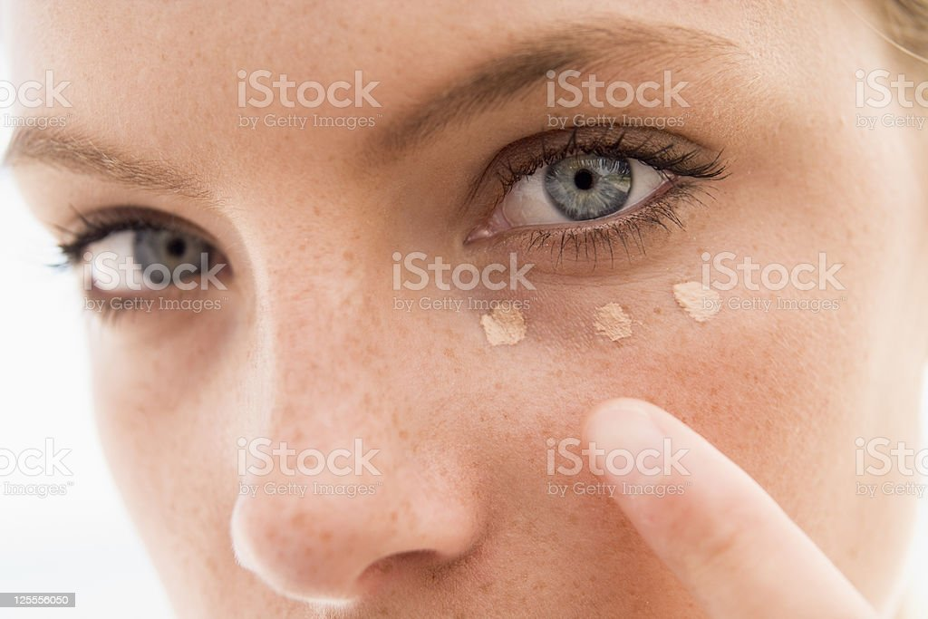 Woman applying concealer stock photo