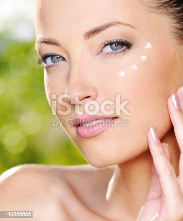 istock Woman applying cosmetic cream near eyes 146888585