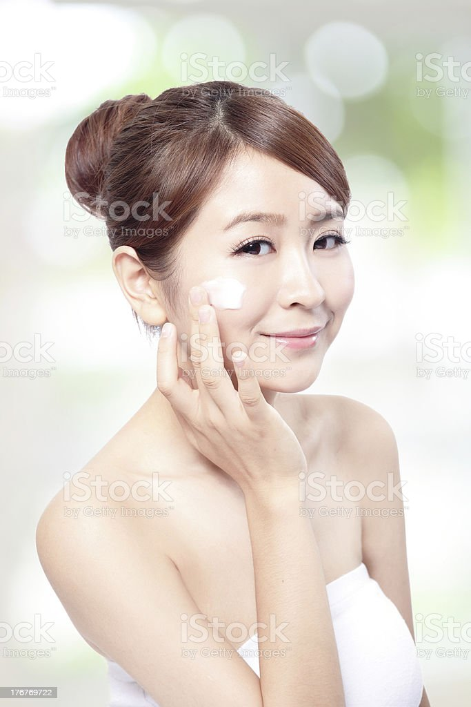 woman applying cosmetic cream on face royalty-free stock photo