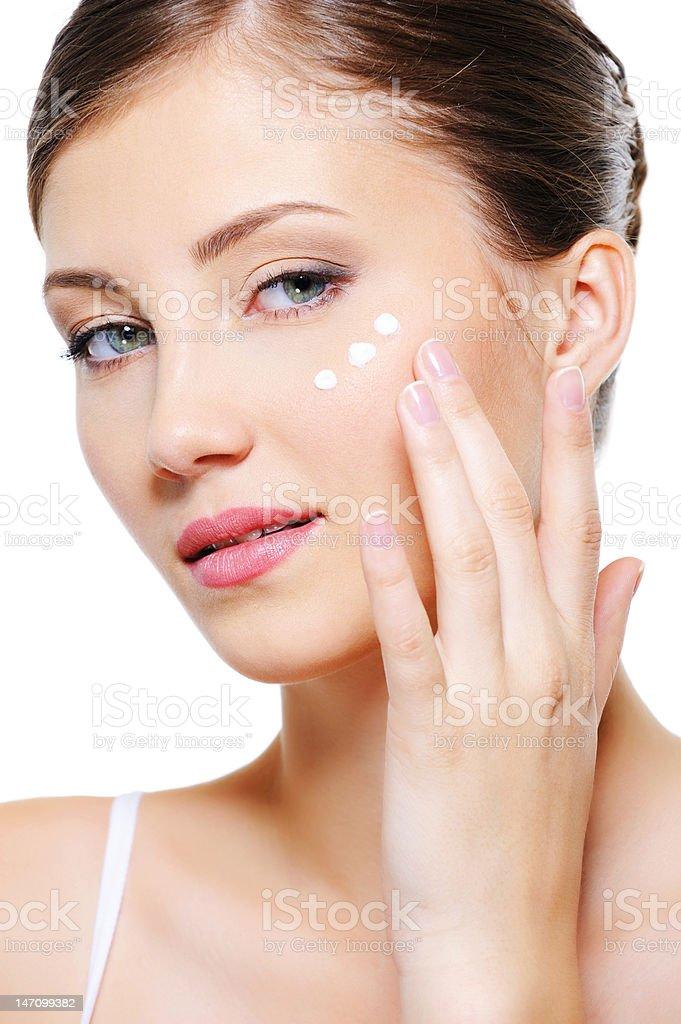 Woman applying cosmetic cream royalty-free stock photo