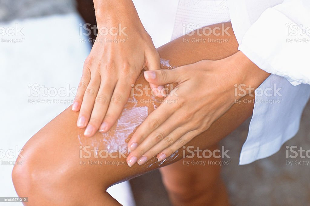 Woman applying cosmetic cream to leg royalty free stockfoto