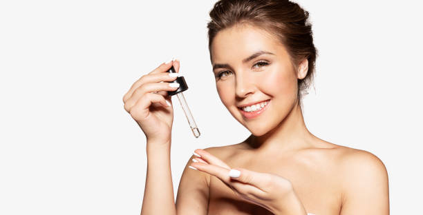 Woman applying cosmetic face oil on hand. stock photo