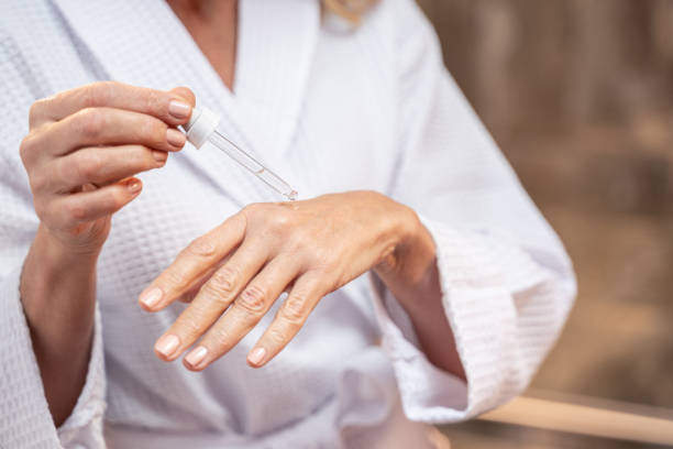 Woman applying cosmetic oil on her hand stock photo