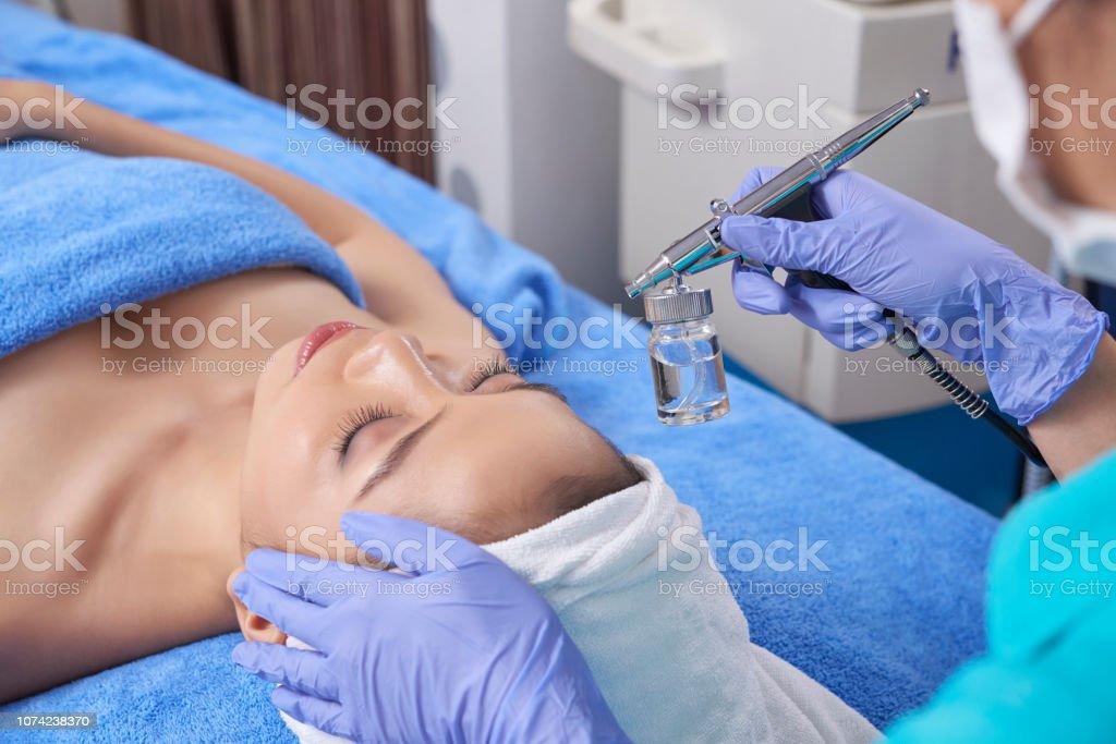 Woman applying cosmetic with sprayer stock photo