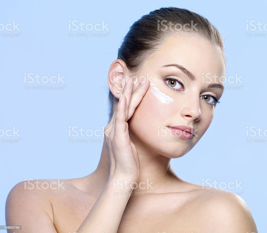 Woman applying cream on face near the eyes stock photo