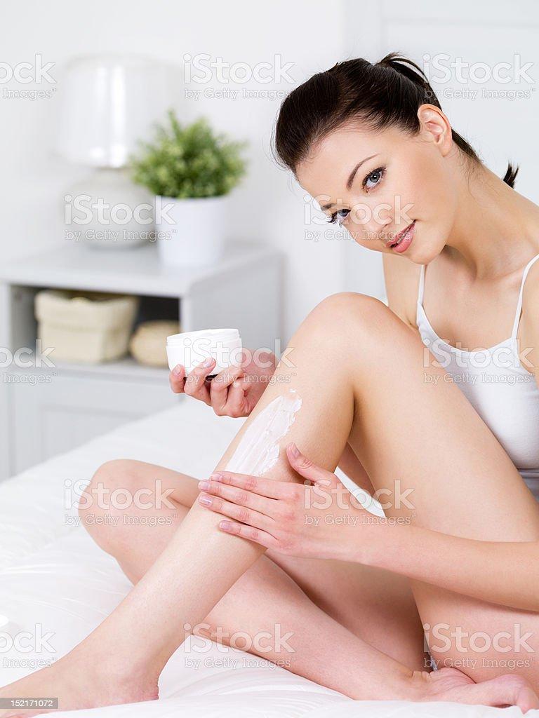 Woman applying cream on her leg royalty-free stock photo